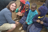 Kenton Lee with children in Kenya trying The Shoe That Grows